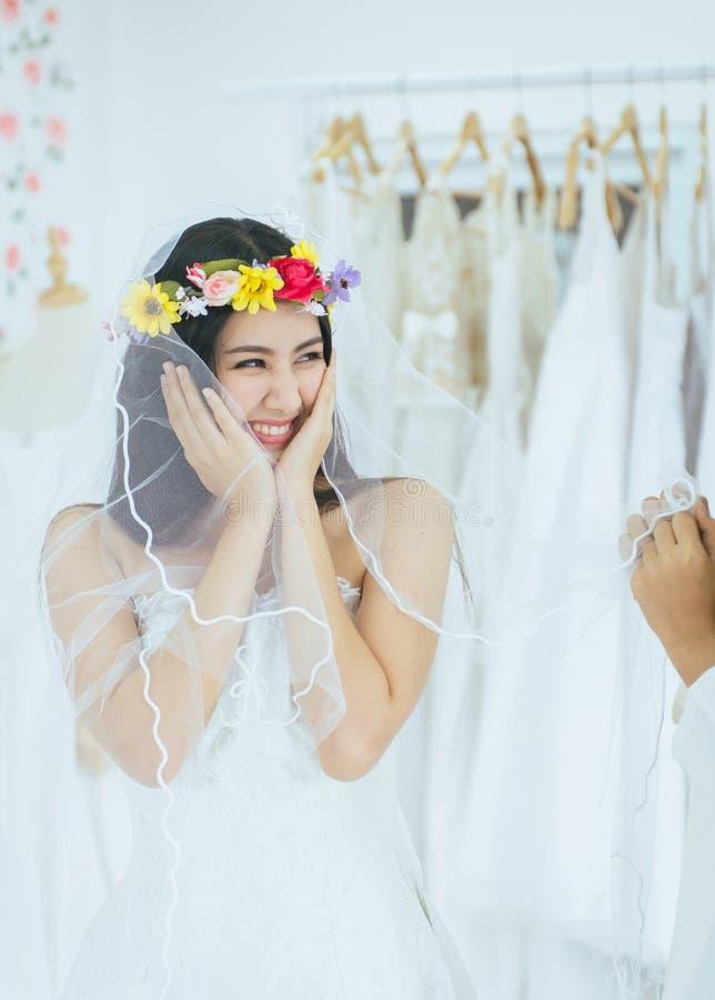 Retrato da noiva asi?tica bonita da mulher no vestido branco alegre e engra?ado, da cerim?nia no dia do casamento, de feliz e no  imagens de stock