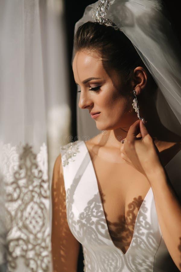 Retrato da noiva bonita em casa Suporte da mulher pela janela no vestido de casamento fotografia de stock