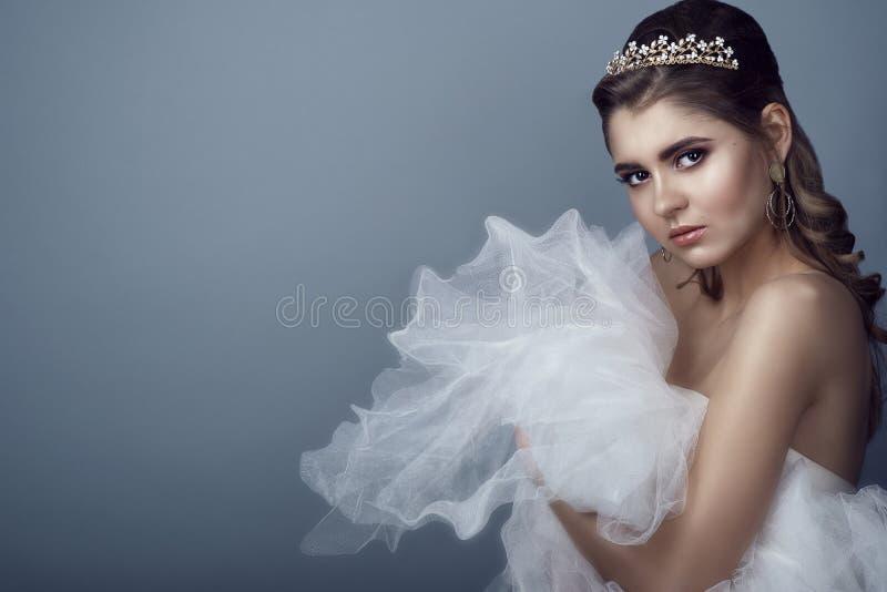 Retrato da noiva bonita nova no diadema com os ombros despidos que abraçam a saia macia de seu vestido de casamento a seu peito imagens de stock