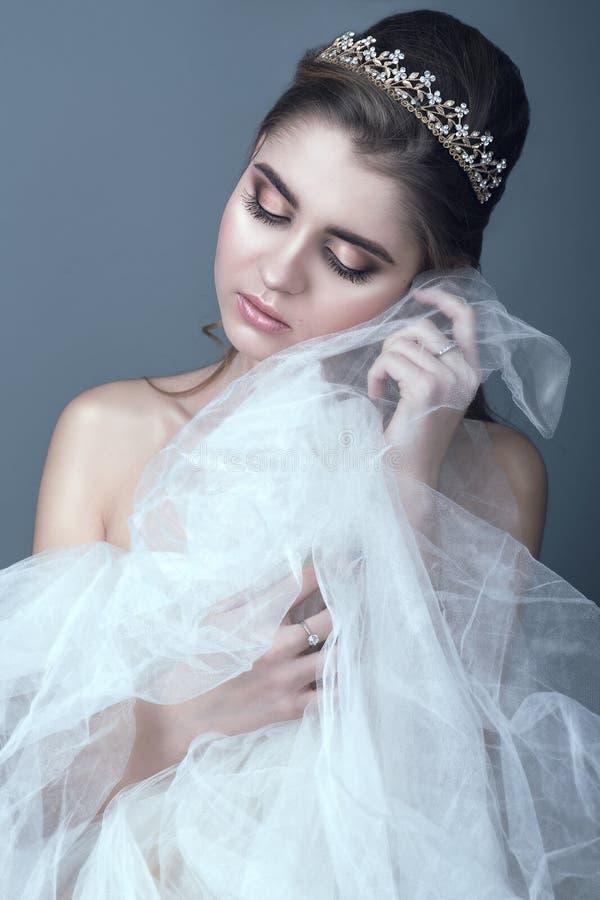 Retrato da noiva bonita nova no diadema com a saia macia tocante dos ombros despidos de seu vestido de casamento com seu mordente imagens de stock