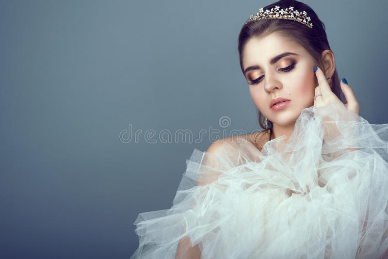 Retrato da noiva bonita nova no diadema que pressiona a saia macia de seu vestido de casamento a seu peito imagem de stock royalty free