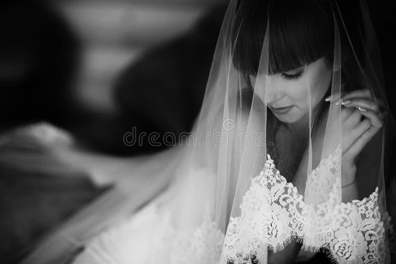 Retrato da noiva de encantamento envolvido em um véu Imagem preto e branco da noiva beuatiful escondida sob o véu fotos de stock