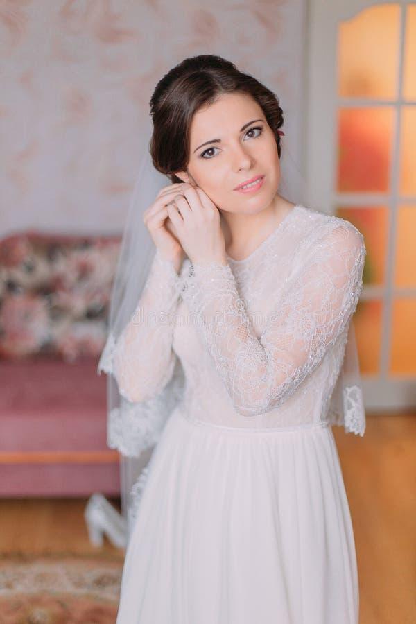 Retrato da noiva encantador no vestido de casamento Jovens mulheres bonitas que vestem seus brincos que preparam-se para a cerimô imagem de stock