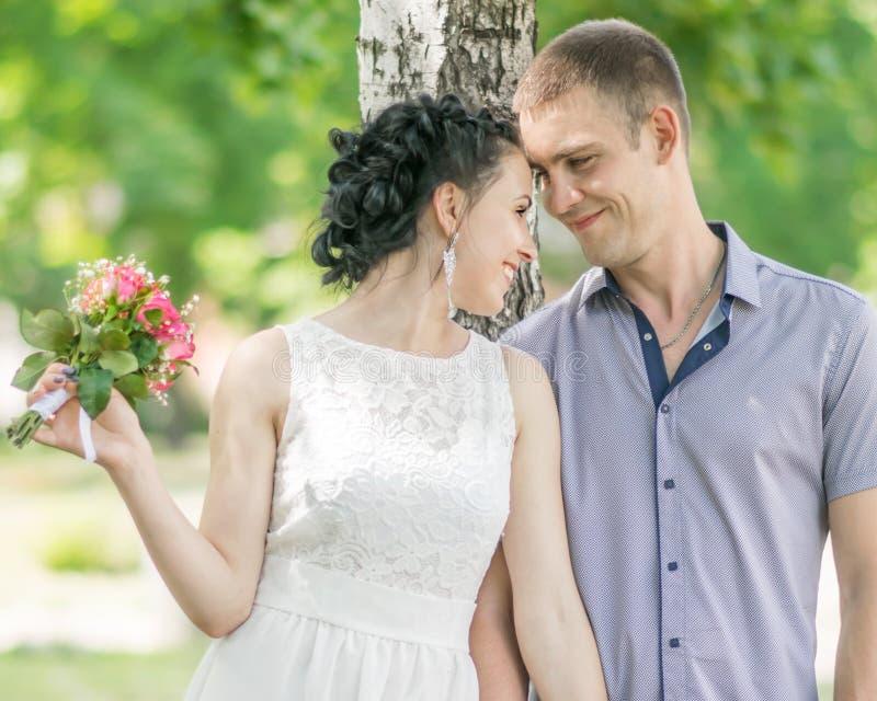 Retrato da noiva fêmea dos pares novos bonitos com sorriso pequeno e olhar do noivo do ramalhete e do homem das rosas das flores  fotografia de stock