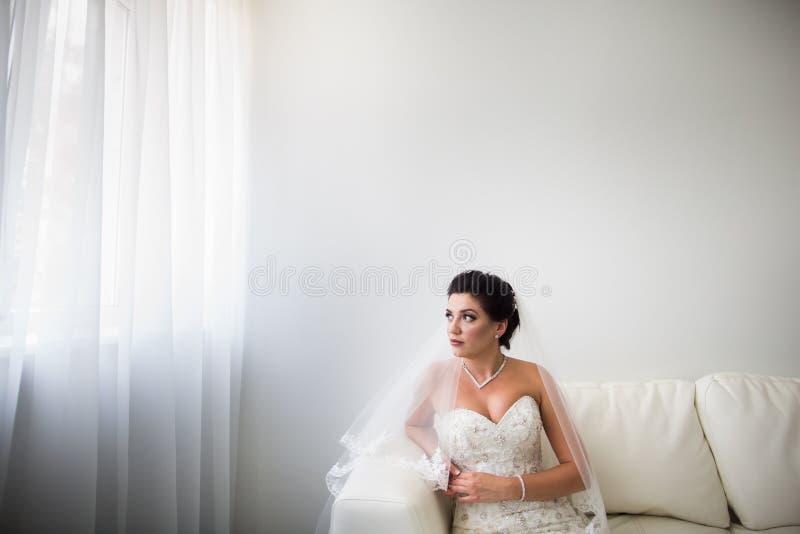 Retrato da noiva feliz bonita que senta-se no sof fotos de stock