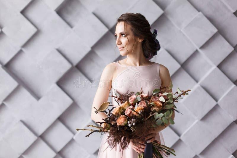 Retrato da noiva Mulher bonita nova que guarda o ramalhete no fundo cinzento geométrico no estúdio foto de stock royalty free