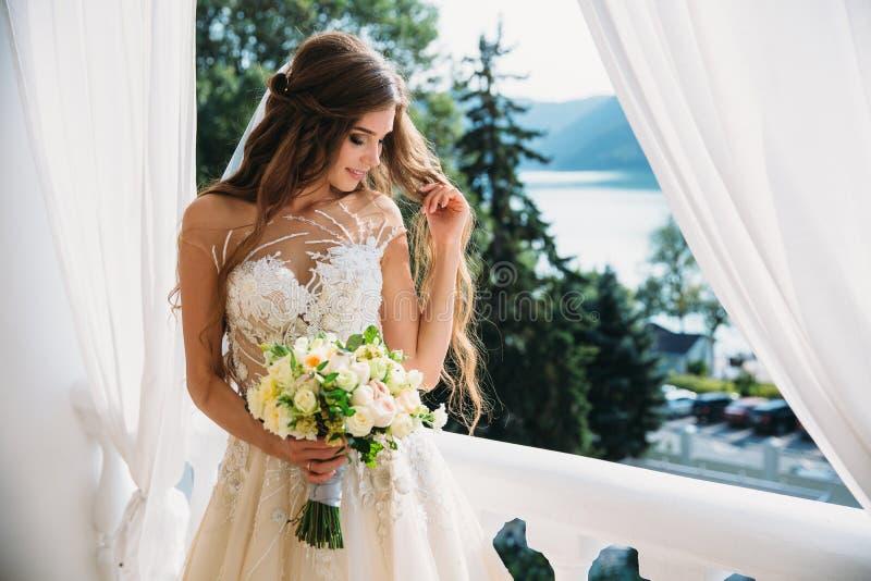 Retrato da noiva nova bonita com o smite bonito no ramalhete branco da posse do vestido de casamento das flores em suas mãos Conc fotos de stock royalty free
