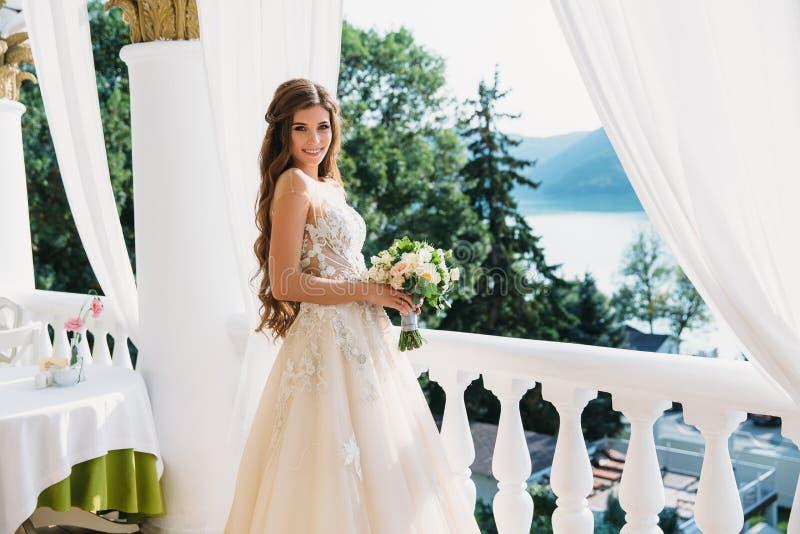 Retrato da noiva nova bonita com o smite bonito no ramalhete branco da posse do vestido de casamento das flores em suas mãos Conc imagem de stock