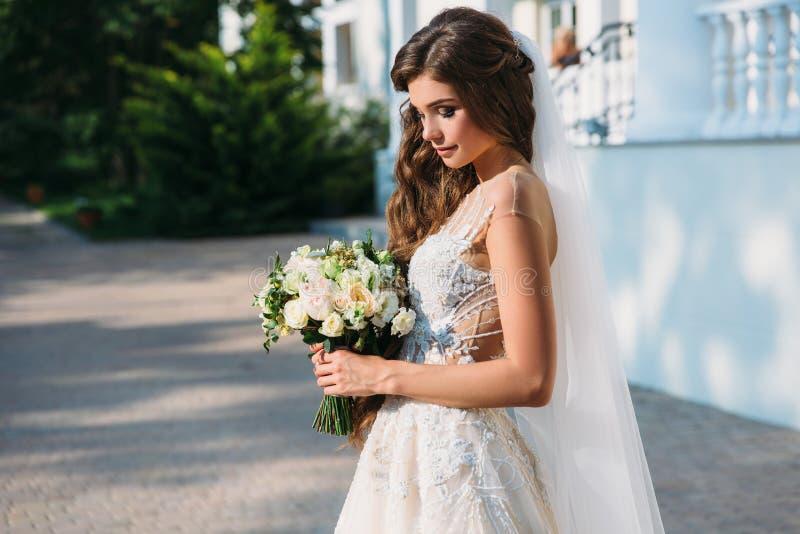 Retrato da noiva nova bonita com o smite bonito no ramalhete branco da posse do vestido de casamento das flores em suas mãos Conc fotografia de stock