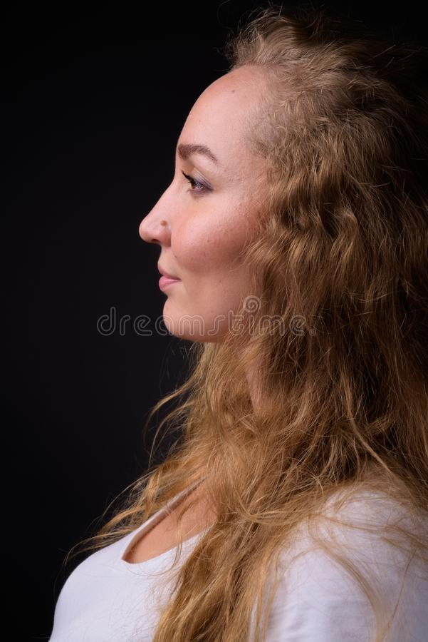 Retrato da opinião do perfil da mulher com cabelo louro ondulado longo fotografia de stock