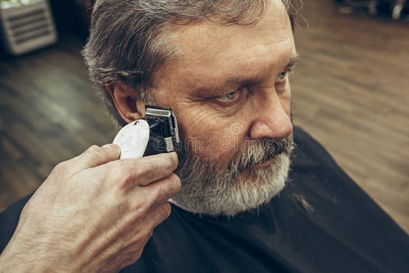 Retrato da opinião lateral do close-up do homem caucasiano farpado superior considerável que obtém a barba que prepara no barbeir foto de stock royalty free