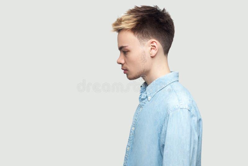 Retrato da opini?o lateral do perfil do homem novo consider?vel s?rio calmo em claro - posi??o azul da camisa e vista para a fren foto de stock