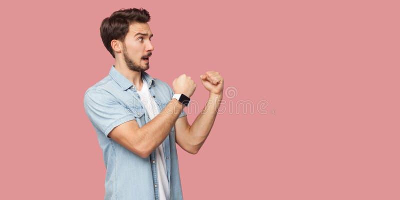 Retrato da opinião lateral do perfil do homem novo farpado considerável irritado na posição azul da camisa do estilo ocasional, o fotografia de stock