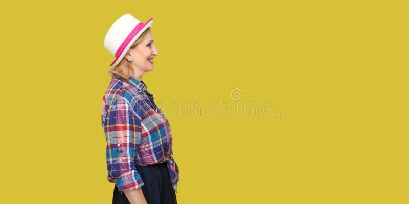 Retrato da opinião lateral do perfil da mulher madura à moda moderna bem sucedida feliz no estilo ocasional com posição do chapéu imagens de stock