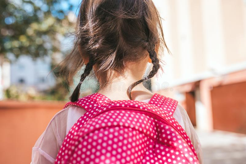 Retrato da opinião traseira do close up do levantamento bonito da criança em idade pré-escolar da menina exterior com a trouxa co imagem de stock royalty free