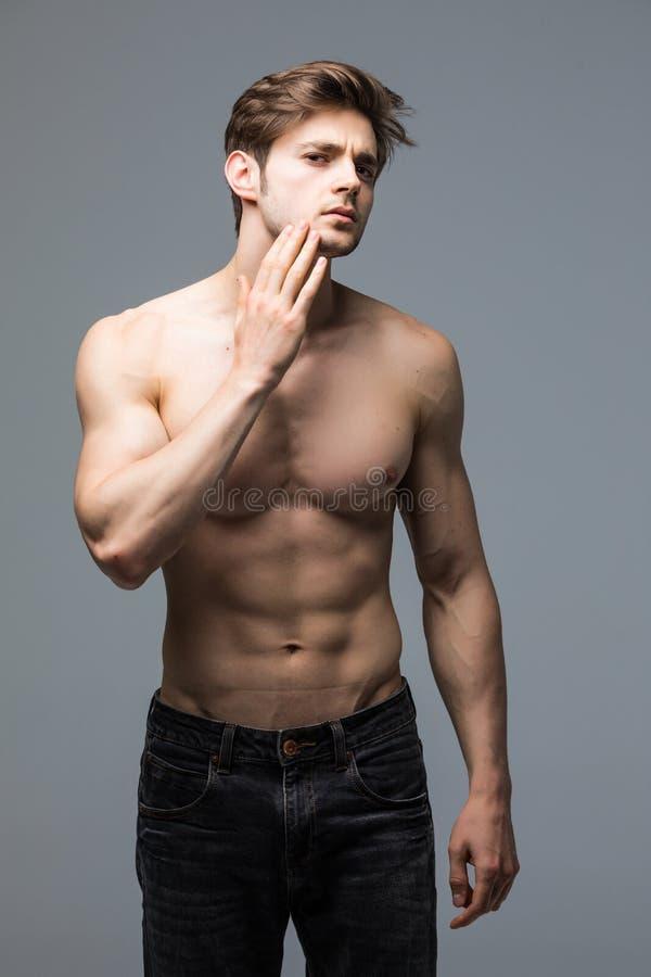 Retrato da parede cinzenta de levantamento modelo da aptidão atlética considerável saudável forte do homem imagens de stock royalty free