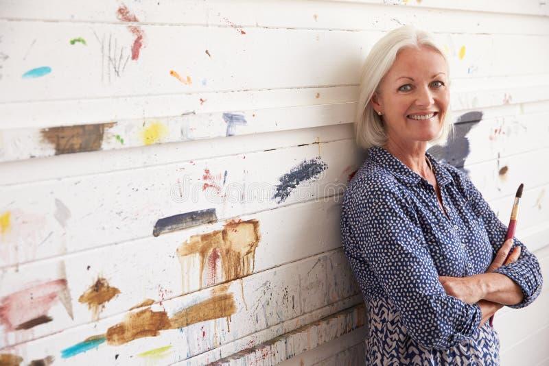 Retrato da parede fêmea de Against Paint Covered do artista imagem de stock