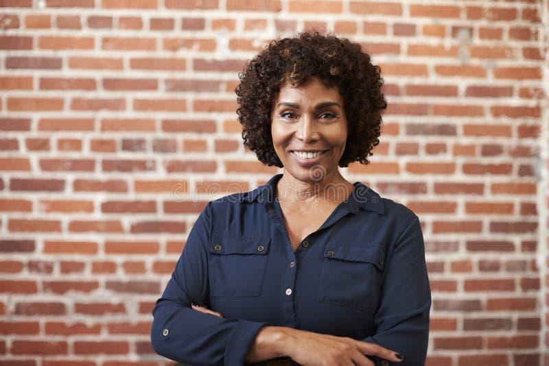 Retrato da parede madura de sorriso de Standing Against Brick da mulher de negócios no escritório moderno imagem de stock