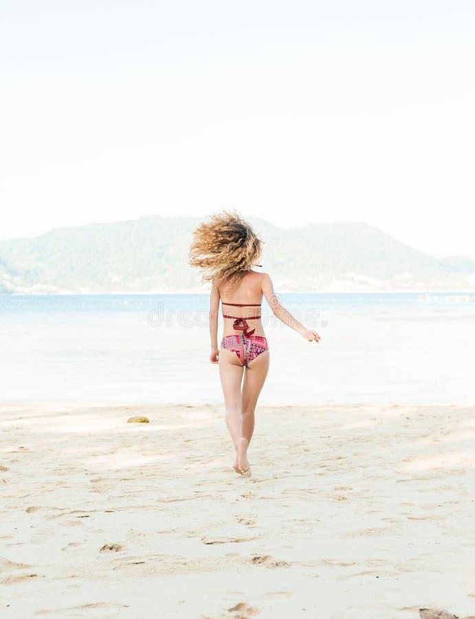Retrato da parte traseira do modelo que senta-se no beira-mar fora fotos de stock