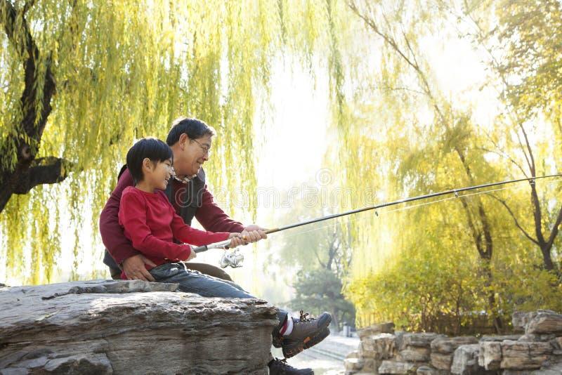 Retrato da pesca do avô e do neto no lago imagem de stock