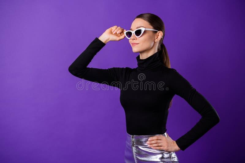 Retrato da pessoa doce concentrada que toca em suas especs. que vestem a gola alta preta isolada sobre o fundo violeta roxo foto de stock