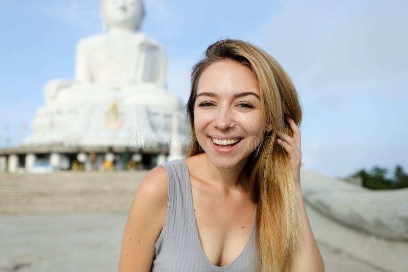 Retrato da pessoa fêmea loura que está perto da estátua concreta branca da Buda em Phuket fotografia de stock