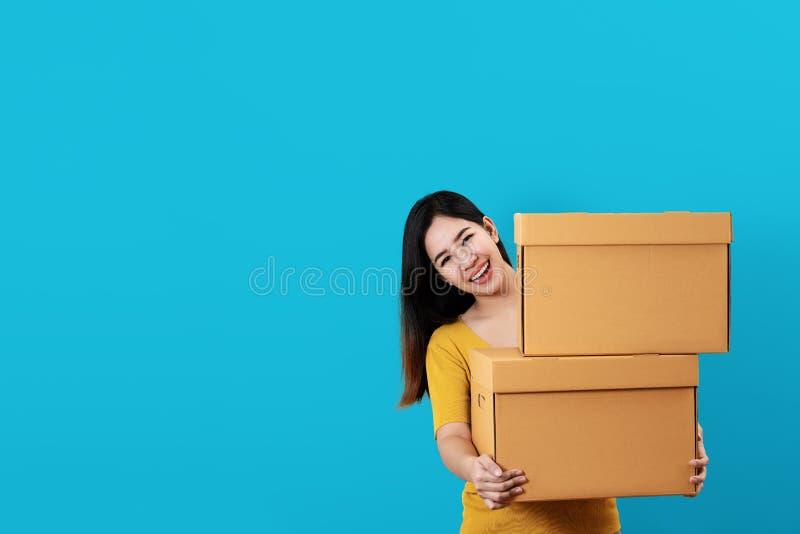 Retrato da pilha de sorriso do empresário asiático novo e guardando ou levando feliz das caixas foto de stock royalty free