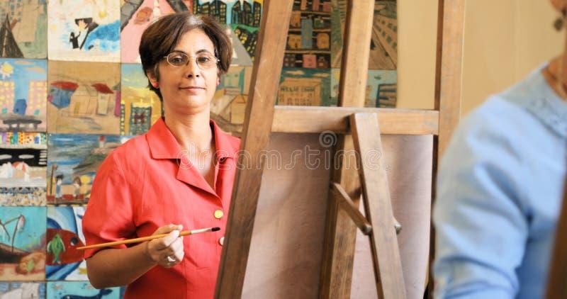 Retrato da pintura de sorriso da mulher feliz em Art School foto de stock royalty free