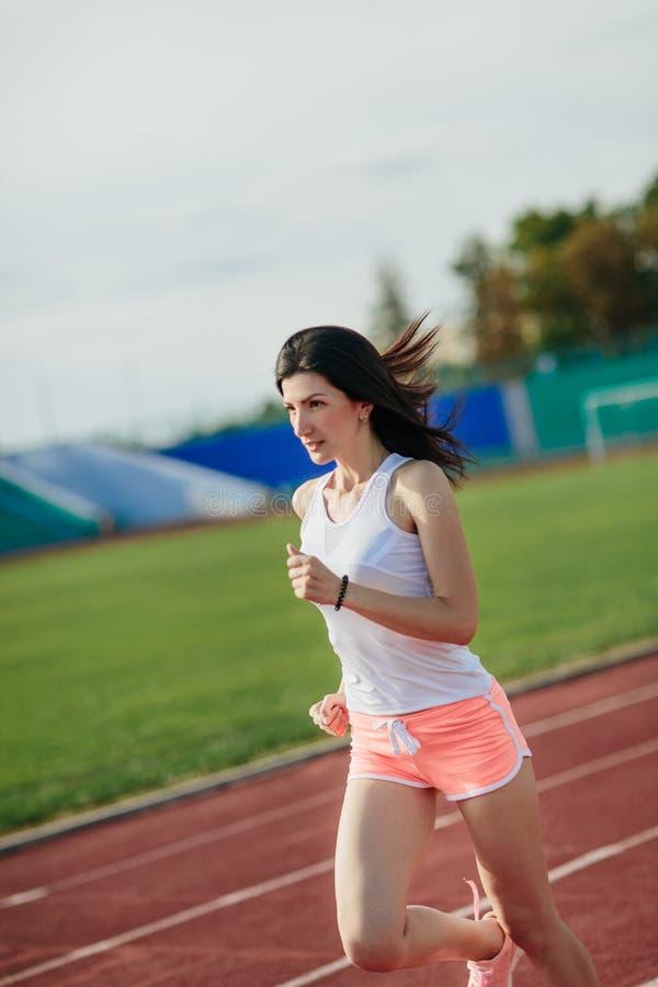 Retrato da pista de atletismo da menina no estádio Opinião dianteira real a jovem mulher no short cor-de-rosa e a camiseta de alç imagens de stock