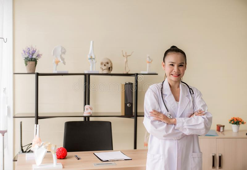 Retrato da posição asiática bonita de sorriso do doutor da mulher e dos braços transversais que olham a câmera no pensamento do h imagens de stock royalty free