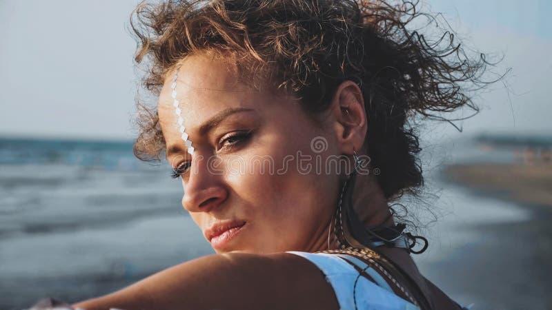 Retrato da posição bonita nova da mulher na praia e da vista no mar imagem de stock