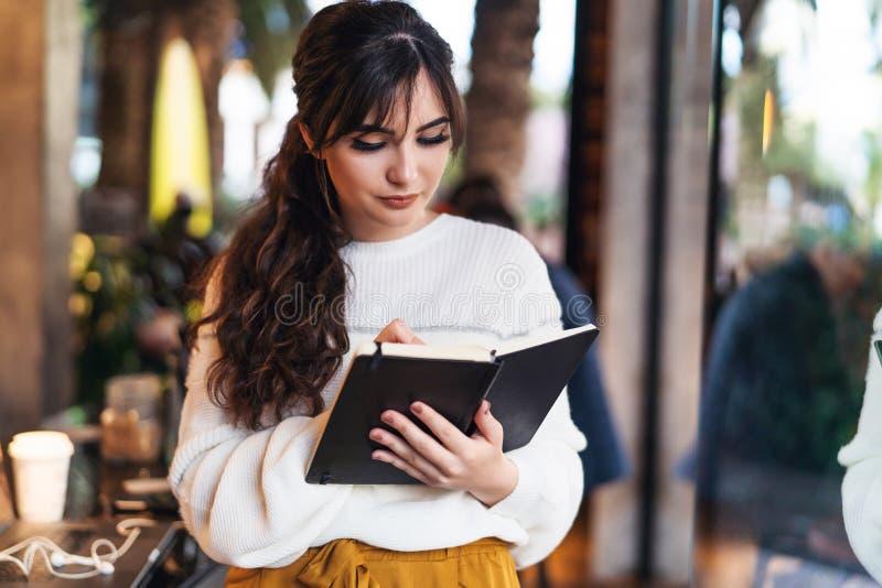Retrato da posição de sorriso nova da mulher no café perto da janela, escrevendo no caderno A menina escreve o diário das notas,  imagem de stock royalty free