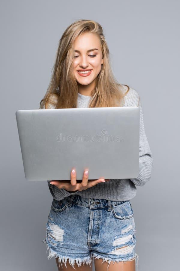 Retrato da posição feliz da mulher com o portátil isolado no fundo cinzento fotografia de stock royalty free