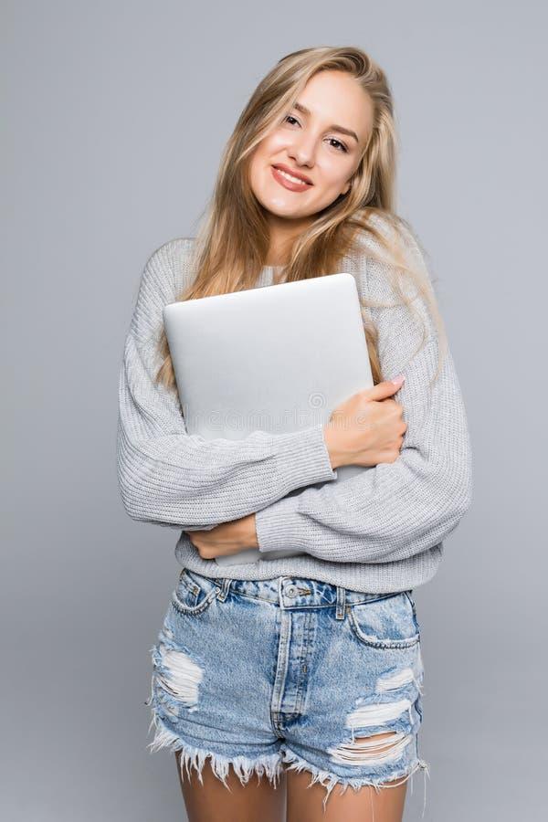 Retrato da posição feliz da mulher com o portátil isolado no fundo cinzento imagem de stock