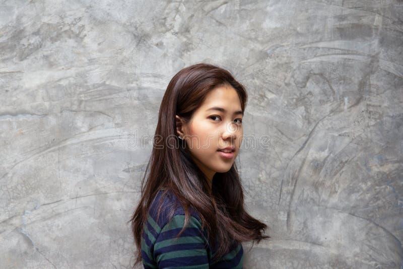 Retrato da posição da mulher do adolescente no muro de cimento cinzento que olha a câmera imagem de stock royalty free