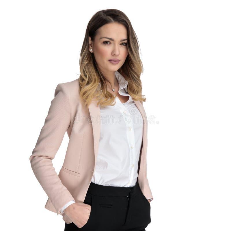 Retrato da posição relaxado da mulher de negócios com mãos em uns bolsos fotografia de stock