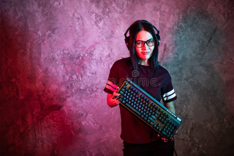 Retrato da pro posição nova bonita da menina do Gamer com um teclado e uns auriculares do jogo e olhares na câmera foto de stock