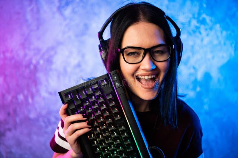 Retrato da pro posição nova bonita da menina do Gamer com um teclado e uns auriculares do jogo e olhares na câmera fotografia de stock royalty free
