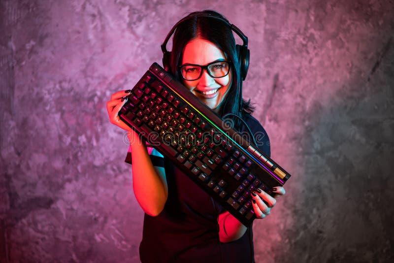 Retrato da pro posição nova bonita da menina do Gamer com um teclado e uns auriculares do jogo e olhares na câmera foto de stock royalty free