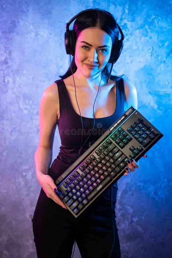 Retrato da pro posição nova bonita da menina do Gamer com um teclado e uns auriculares do jogo e olhares na câmera fotos de stock