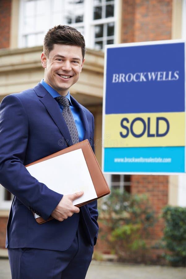 Retrato da propriedade residencial da parte externa ereta masculina do corretor de imóveis com Sig vendidos imagem de stock