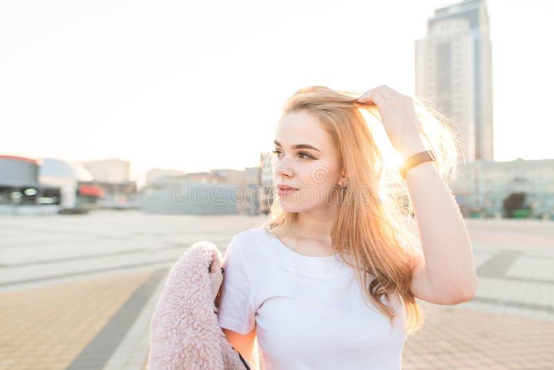 Retrato da rua de uma menina atrativa em um t-shirt branco, estando no quadrado de cidade no por do sol foto de stock