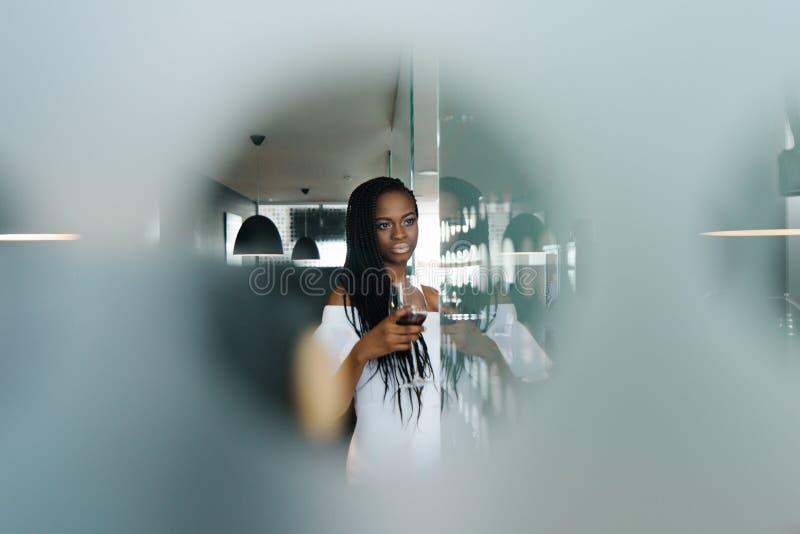 Retrato da senhora africana à moda adorável no vestido branco elegante que aprecia o vinho tinto imagem de stock
