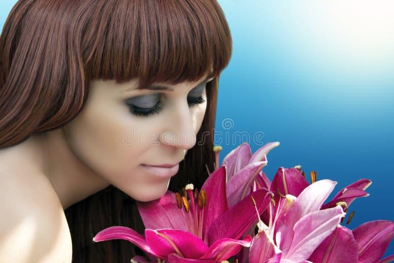 Retrato da senhora bonita que olha flores e que cheira as fotografia de stock royalty free
