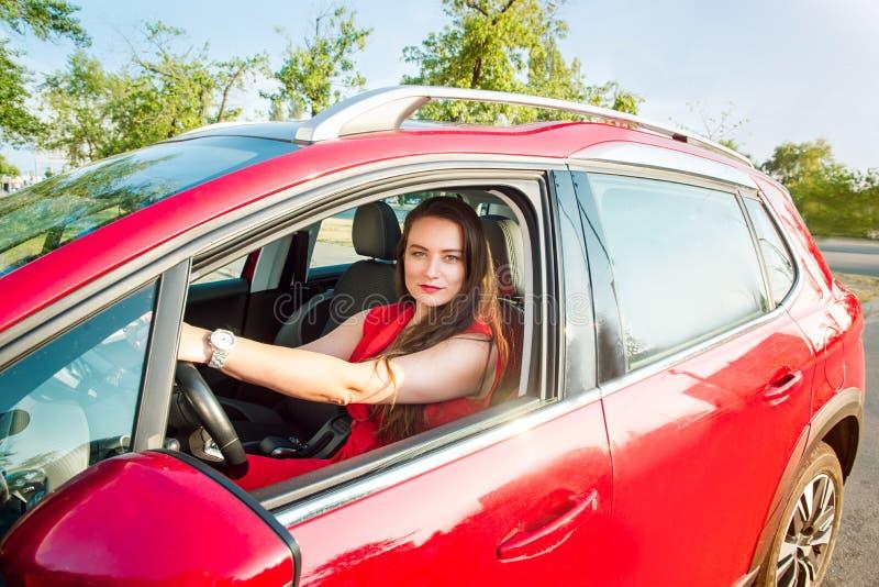 Retrato da senhora de sorriso do negócio, motorista caucasiano da jovem mulher na roupa vermelha que olha a câmera e que sorri ao fotografia de stock