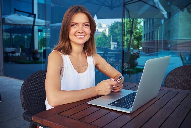 Retrato da senhora de sorriso que senta-se no terraço aberto do café com lapt imagem de stock royalty free
