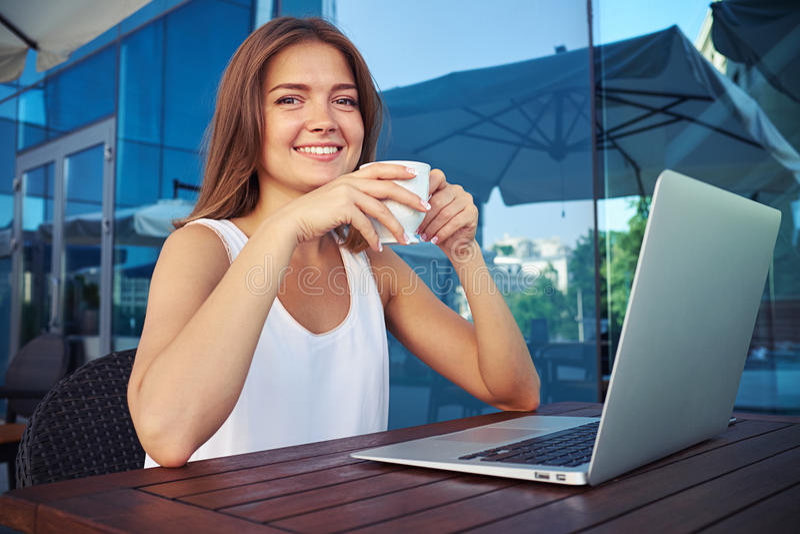 Retrato da senhora de sorriso que senta-se no terraço aberto do café com lapt foto de stock royalty free