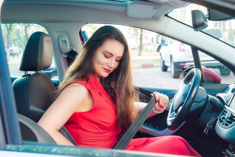 Retrato da senhora do negócio, motorista caucasiano da jovem mulher na correia de banco de carro vermelha da asseguração do terno fotos de stock royalty free