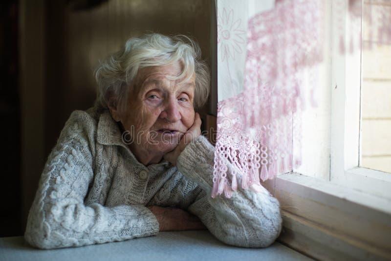 Retrato da senhora idosa que senta-se na tabela imagem de stock