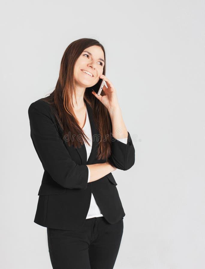 Retrato da senhora moreno de sorriso nova da mulher que fala no móbil foto de stock royalty free